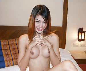 Busty thai ladyboy posing on the bed after shower